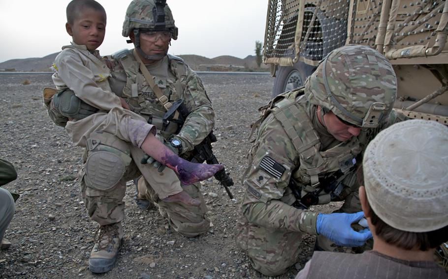 Sgt. Ramon Cortez, 38, a forward observer from El Paso, Texas, holds a young Afghan boy whose foot was badly burned. Injuries such as burns and broken fingers are often treated by Afghan doctors with little more than colored dye in this part of Khost province, despite the fact there is a government hospital less than 10 miles away down the paved road seen in the background.
