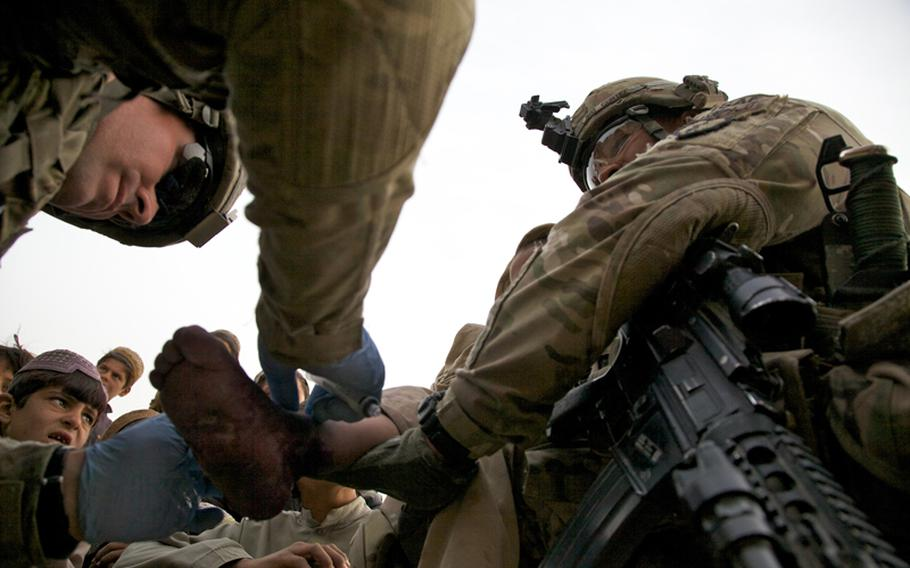 Sgt. Ramon Cortez, 38, a forward observer from El Paso, Texas, holds an Afghan boy while Spc. Joe Kunsch, left, a 34-year-old medic from Prescott, Ariz., cleans dirt and grime from his burned foot. Both are members of 1st Platoon, Battery A, 2nd Battalion, 377th Parachute Field Artillery Regiment, part of the 4th Brigade Combat Team (Airborne), 25th Infantry Division.