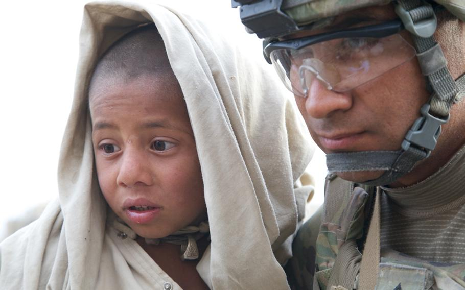 Sgt. Ramon Cortez, 38, a forward observer from El Paso, Texas, holds a young boy with two burned feet as a medic treats the wounds. Despite the severity of the burns, the boy barely flinched while the medic worked on him.