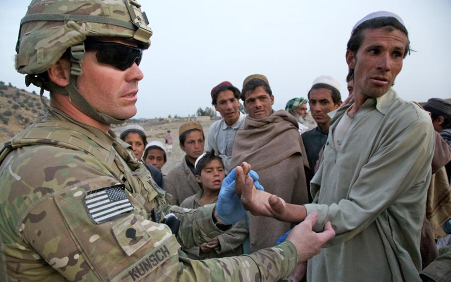 An Afghan man listens as Spc. Joe Kunsch, a 34-year old medic from Prescott, Ariz., explains he can't do anything for his finger. The man broke the finger a month earlier and didn't seek treatment. Instead, he doused it with henna, a natural dye commonly used to treat wounds in the part of Afghanistan's Khost province. Kunsch says the dye probably doesn't hurt, but certainly doesn't help.