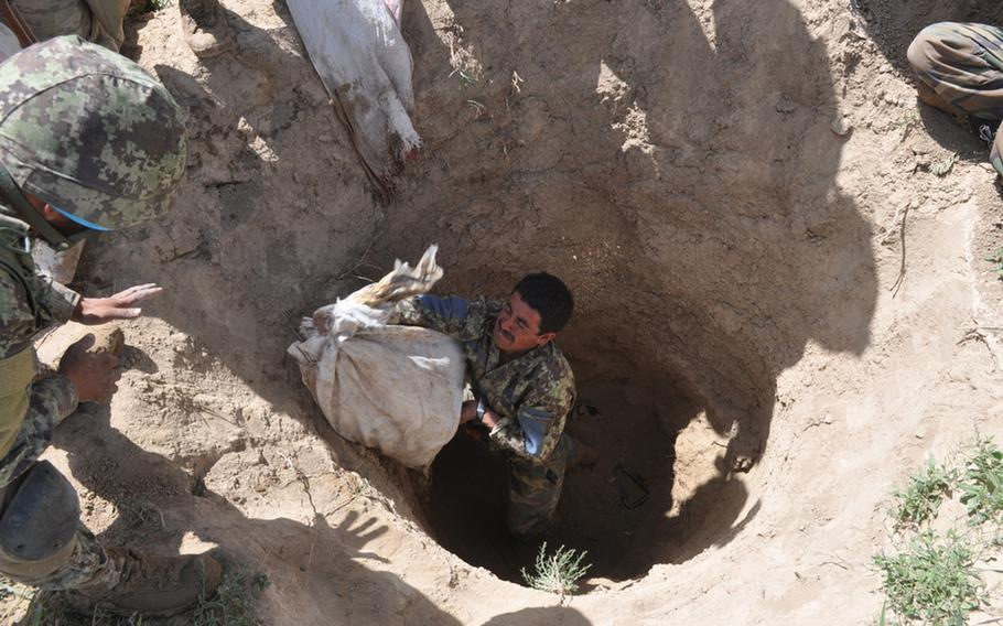 An Afghan soldier removes a bag of bomb-making materials stashed by insurgents in a farm field near the village of Muqur in Ghazni province. Col. Mohammad Wasil, the former commander of the battalion to which the soldier belongs, is suspected of selling weapons to militants.