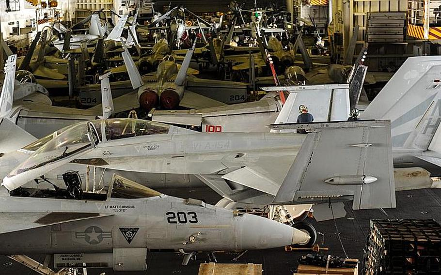 Aircraft assigned to Carrier Air Wing (CVW) 11 sit in the hangar bay aboard the USS Nimitz (CVN 68) Sept. 23 2013 while the ship sails in the U.S. 5th Fleet area of responsibility.