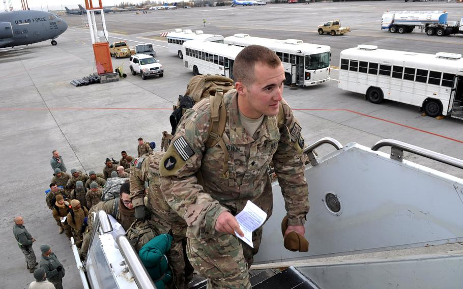 """Troops on their way home after deployments in Afghanistan board a flight at Manas International Airport near Bishkek, Kyrgyzstan. After serving as the """"Gateway to Afghanistan"""" for more than a decade, the U.S. Air Foce facility at Manas will close down in a matter of months."""