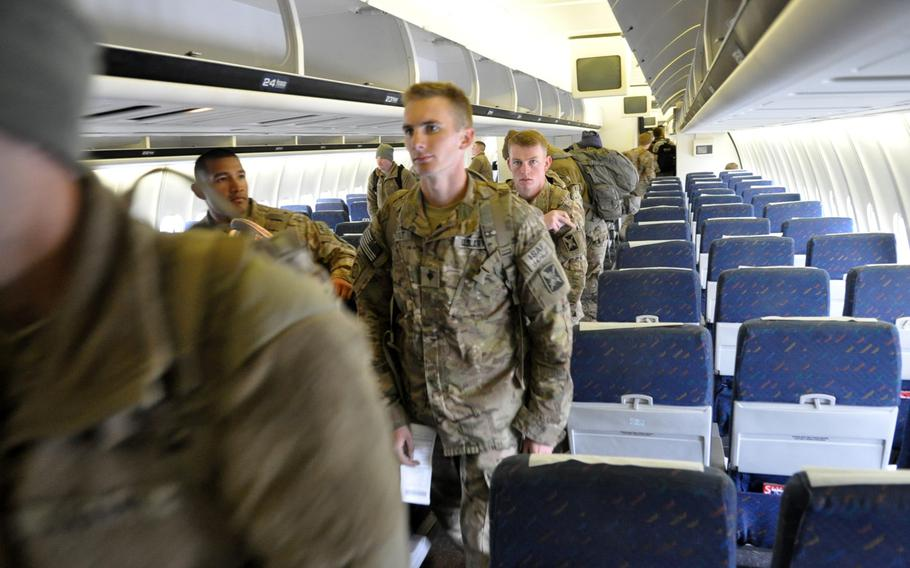 Troops leaving deployments in Afghanistan find their seats on a civil airliner at Manas International Airport in Kyrgyzstan. The U.S. Air Force facility at the airport processes as many as 2,000 service members a day on their way in and out of Afghanistan.