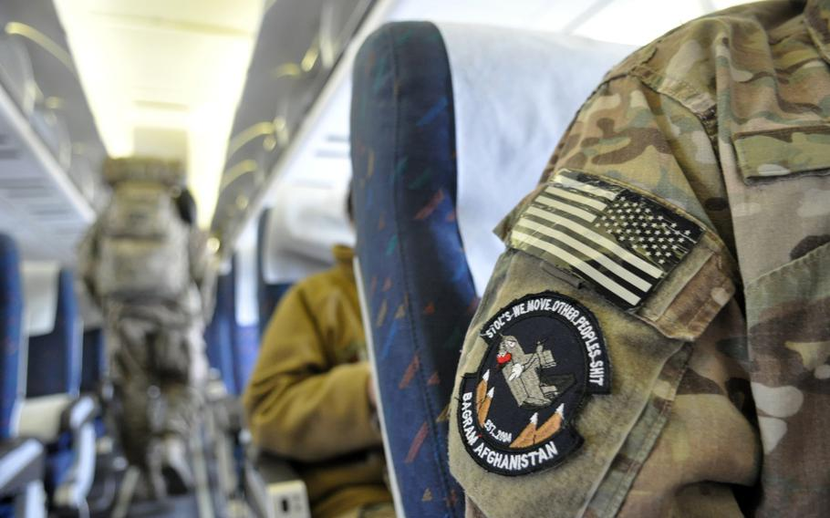 Troops settle into their seats aboard a civil airliner for a flight departing from Manas International Airport in Kyrgyzstan, on a trip bound for Europe and eventually, the United States.