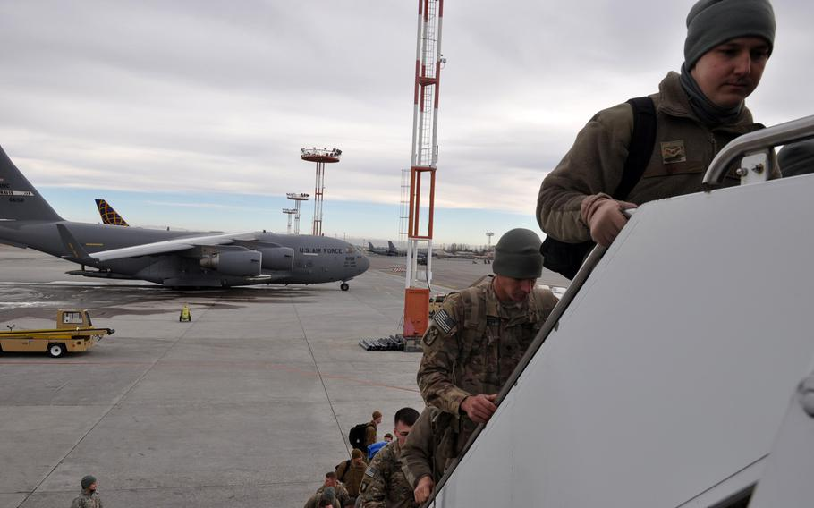 Service members board an aircraft at Manas International Airport in Kyrgyzstan after leaving deployments in Afghanistan. The U.S. Air Force facility at the airport has operated as a key logistics hub since the beginning of the war in Afghanistan.
