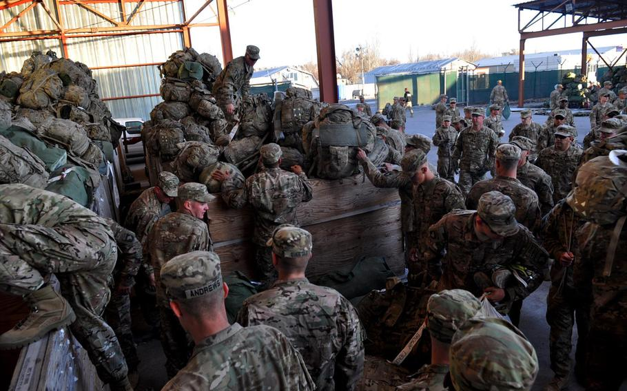 Soldiers from the 1st Battalion, 506th Infantry Regiment, 101st Airborne Division, dig through wooden bins full of duffel bags and backpacks as they prepare for customs inspections at Manas Transit Center in Kyrgyzstan.