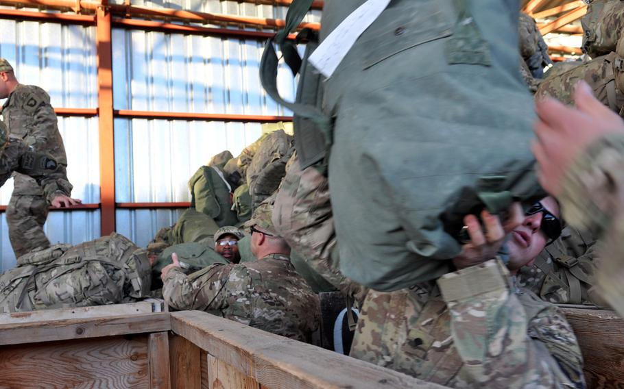 Soldiers from the 1st Battalion, 506th Infantry Regiment, 101st Airborne Divisio, pull duffel bags and backpacks from wooden bins as they prepare for customs inspections at Manas Transit Center in Kyrgyzstan.
