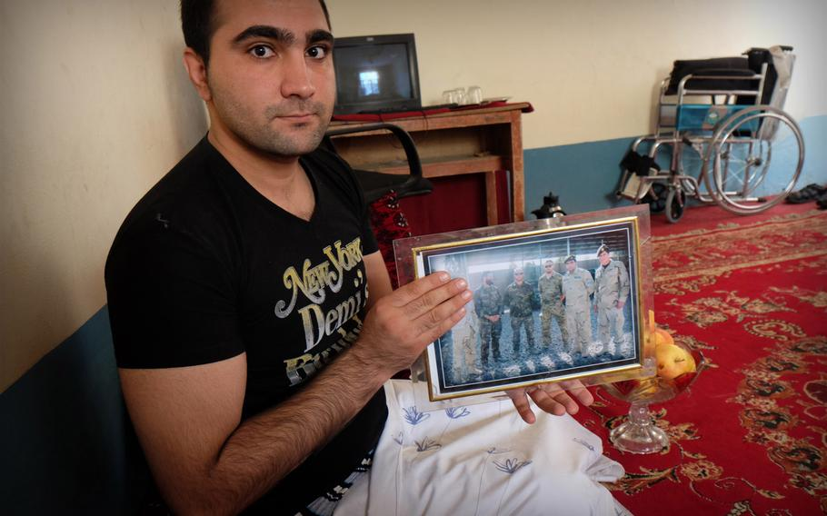 Qandagha Qandaghari, a former commander of an elite police unit, displays a photo of international military advisers with whom he worked before losing both his legs to a roadside bomb in Helmand in the summer of 2014. He says he feels frustrated that he hasn't been able to apply his education and training to another job in the security forces.