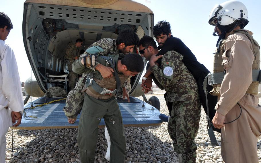 Afghan National Army soldiers and Afghan Air Force airmen help carry wounded soldiers into the back of an Mi-17 helicopter at Camp Leatherneck in southwest Afghanistan in June 2013. Afghan security forces have faced rising casualties as international troops depart and fighting continues.