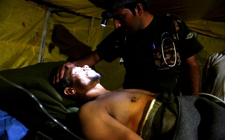 An Afghan army medic examines a local policeman who was critically injured last month when he was shot during a joint operation in Nangarhar province. Limited resources meant the army could not evacuate him to a better hospital.