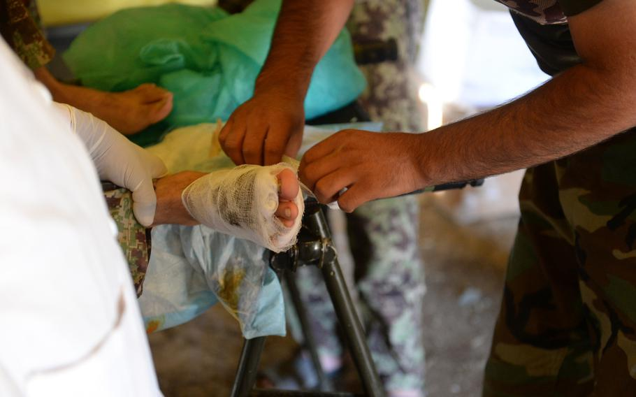 An Afghan army medic bandages the foot of a soldier injured during an operation in Nangarhar province last month. Wounded soldiers and police were treated at this forward aid station, but then often had to wait hours or even a day to be evacuated to a better hospital.