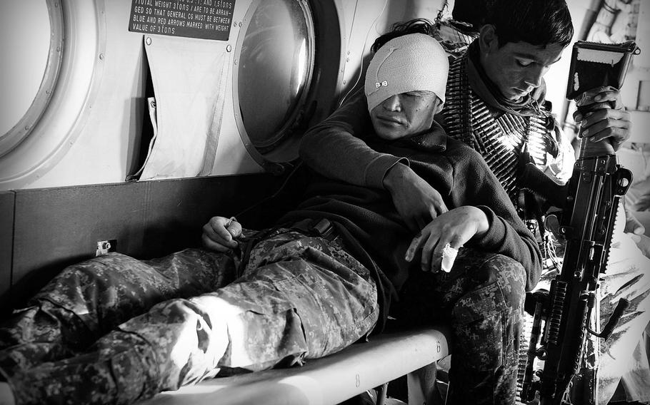 Inside an Afghan Air Force Mi-17 helicopter, a soldier comforts a comrade injured by an improvised bomb in Uruzgan province on Jan. 6, 2014. Afghan security forces have taken the brunt of casualties in the unfinished war as international troops have withdrawn.