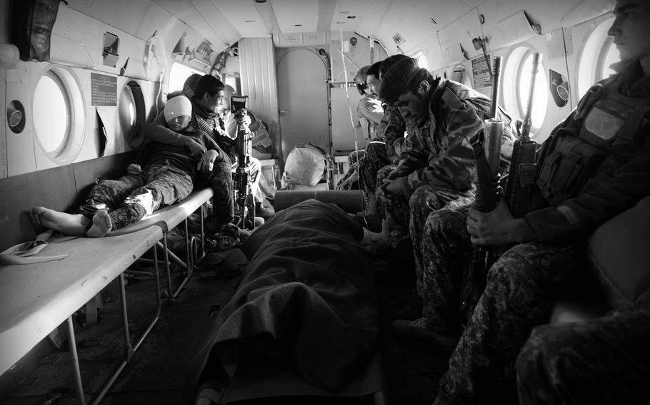 Afghan National Army soldiers rest in the back of an Mi-17 helicopter after being evacuated from a remote outpost in southern Afghanistan. As coalition air support has dwindled to almost nothing, the few Afghan Air Force helicopters are in high demand.