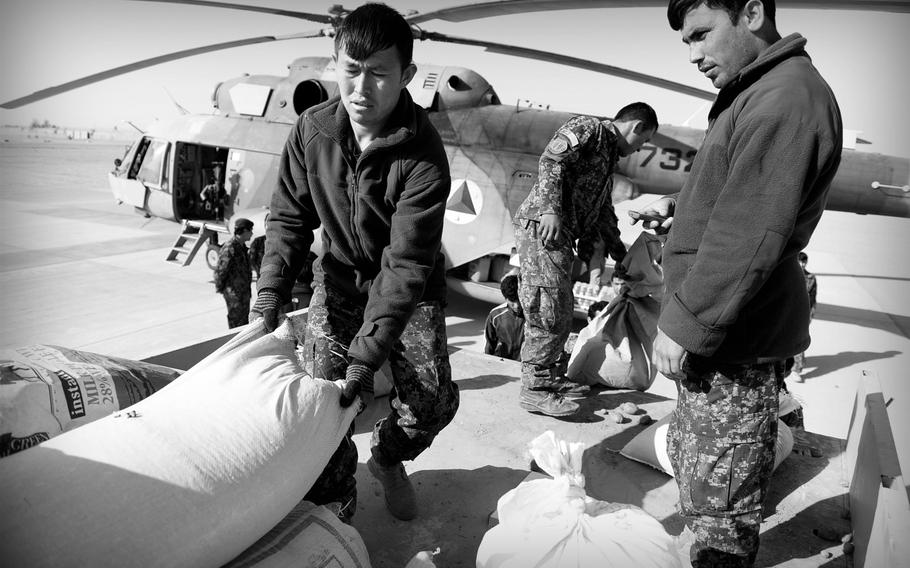Afghan National Army soldiers unload food and other supplies from a truck onto a waiting Mi-17 helicopter at a desert base in southern Afghanistan. The over-stretched Afghan Air Force has only a handful of aircraft to not only supply remote outposts, but evacuate wounded and transport troops.