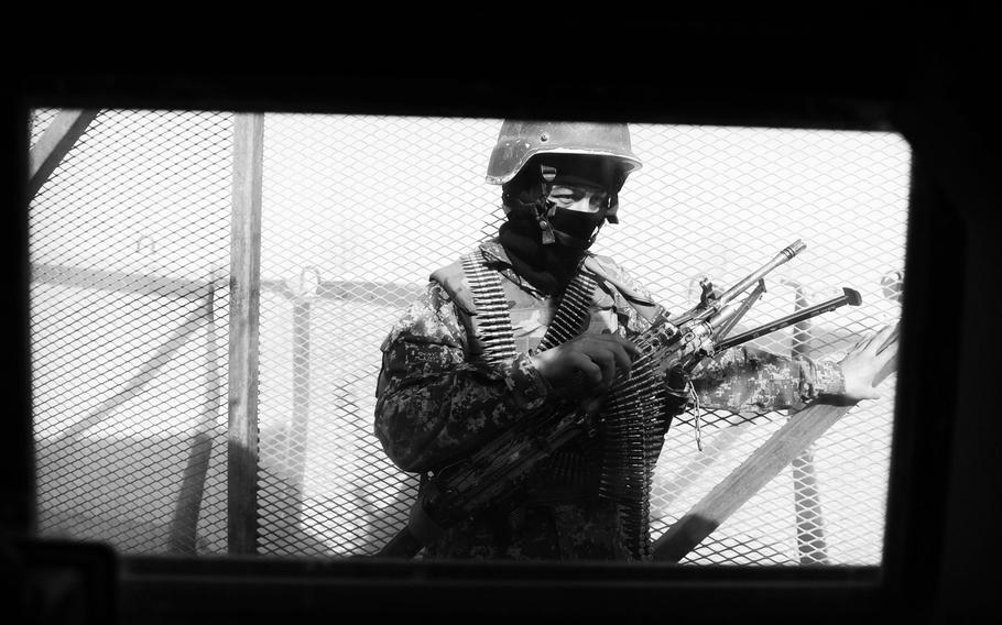 An Afghan National Army soldier guards the gate at the former American forward operating base in Masum Ghar. Coalition forces abandoned hundreds of bases around Afghanistan, many of which are now used by the ANA.
