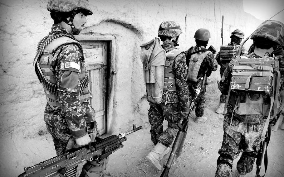 Afghan soldiers patrol a village in Panjwai district in southern Afghanistan on Jan. 5, 2015. Officials say a push to maintain a regular presence by security forces has led to a decrease in Taliban influence in the area.