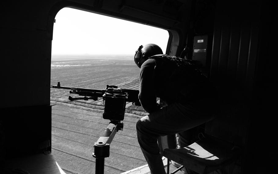 An Afghan Air Force crew chief scans for threats from the door of an Mi-17 helicopter over Kandahar province in southern Afghanistan. With the departure of most foriegn troops, such aircraft provide vital support for security forces scattered around the country.