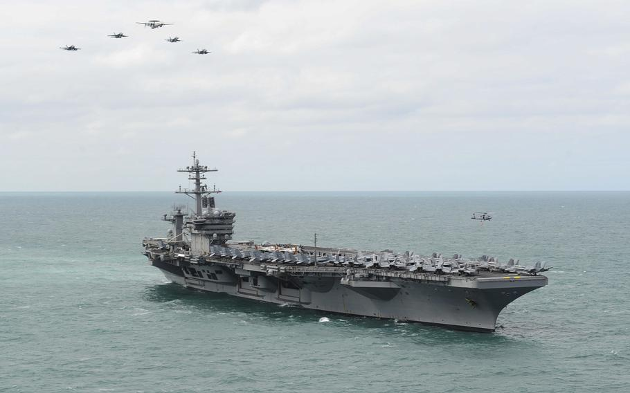 Aircraft embarked aboard the USS Theodore Roosevelt fly in formation over the carrier on Sunday, March 22, 2015, during a visit to the British coast near Portsmouth, England.