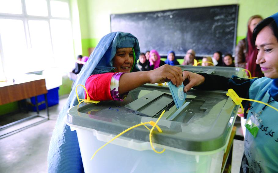 An Afghan woman casts the last ballot at a high school in central Kabul during the national elections held on Saturday, April 5, 2014. Women made up a significant part of the turnout at polling stations across the city.