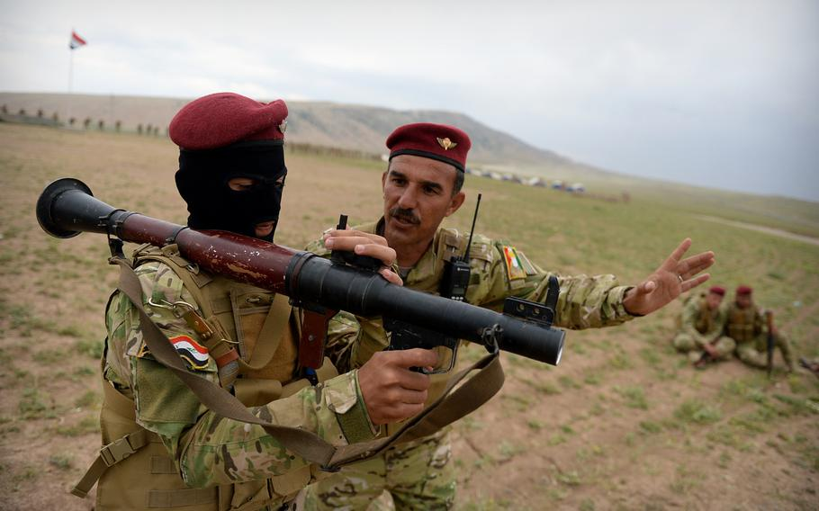 An instructor teaches a volunteer fighter how to operate a rocket-propelled grenade launcher at a camp in northern Iraq run by Turkish advisers and exiled leaders from Mosul. The makeshift camp can train as many as 1,000 fighters at a time.