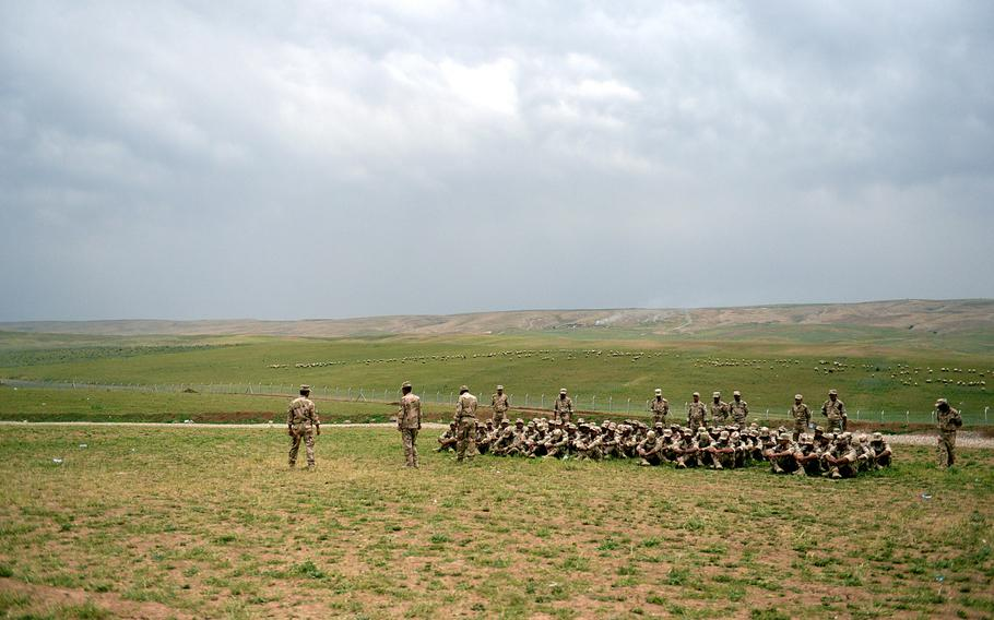 As sheep graze in the background, volunteer fighters listen to an instructor at a camp in northern Iraq. The volunteers, who are training to fight the Islamic State group, have only a few broken weapons to train with.