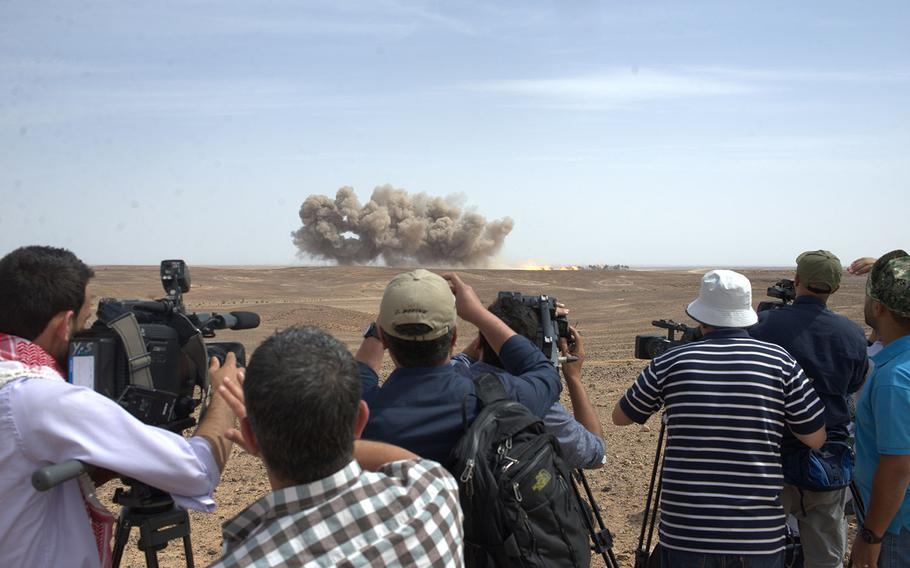 Press members watch the impacts from a B-52 bombing at the Wadi Shadiya training range in Jordan on May 18, 2015, as part of an exhibition of American and Jordanian military firepower held before officials from both countries. The event is the culminating act of the exercise Eager Lion, which is held annually in Jordan to signal U.S. support for the key Middle East ally.
