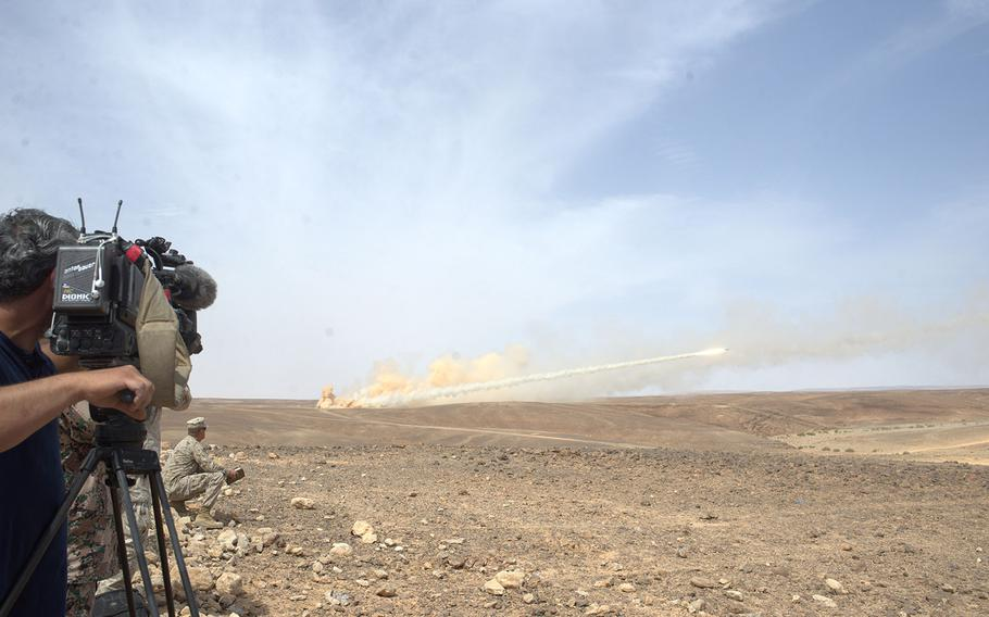 A cameraman films a Jordanian High Mobility Artillery Rocket System (HIMARS) on the Wadi Shadiya training range in Jordan on May 18, 2015, during an exhibition of American and Jordanian firepower before officials from both nations. The event is the culminating act of the exercise Eager Lion, which is held annually in Jordan to signal U.S. support for the key Middle East ally.