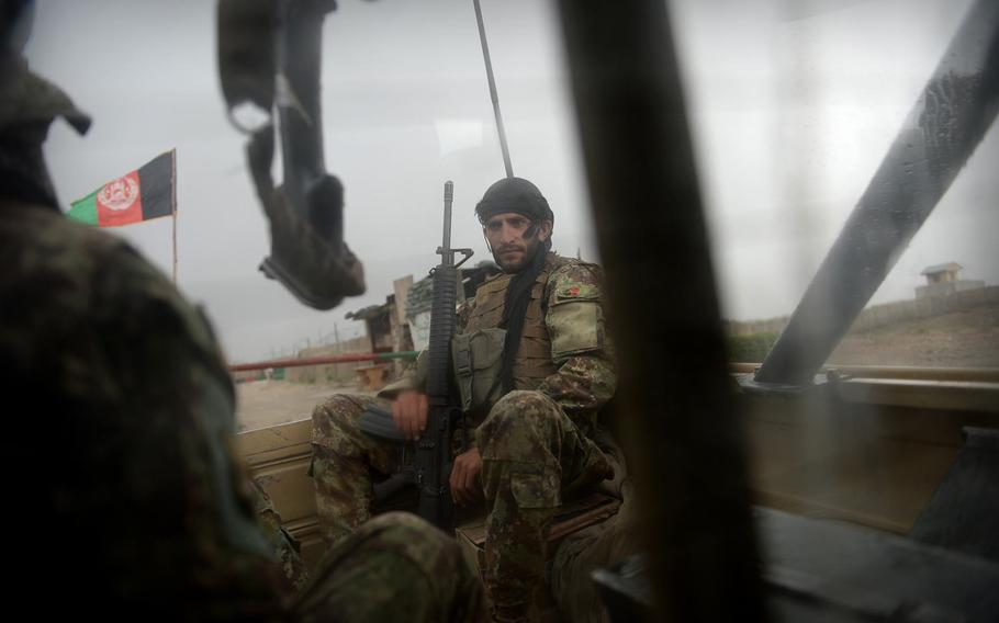 An Afghan soldier braves a summer rain storm in the back of a Ford pickup truck on a mission in Nangarhar province in August 2015. Afghan security forces face a rough life in the field on top of daily danger from insurgent bombs and ambushes.