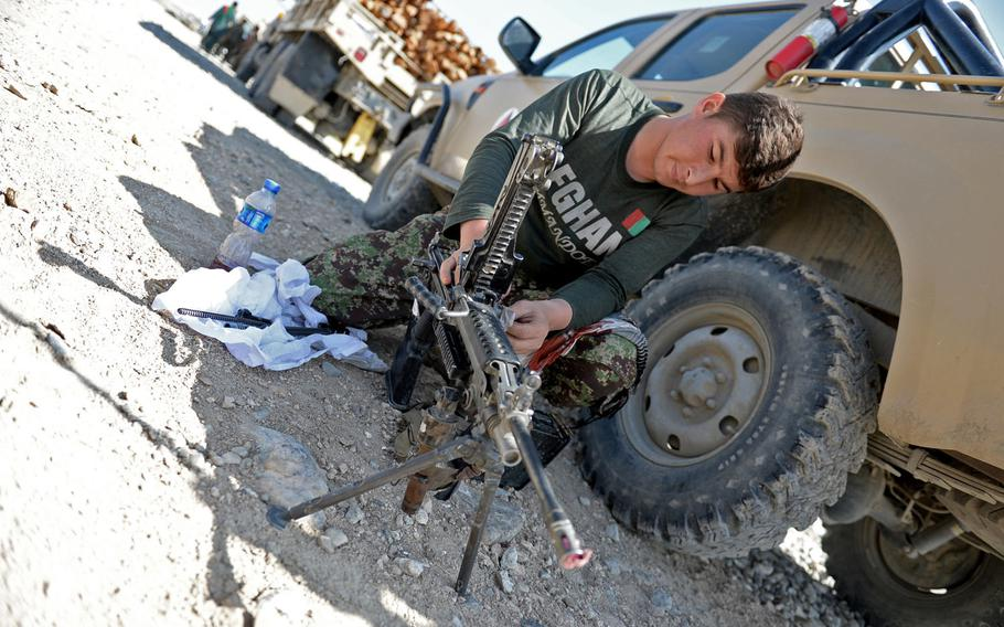 Naiemullah, an Afghan soldier with the 4th Brigade, 201st Corps, cleans his gun before a mission escorting a supply convoy in Nangarhar province in August 2015. From January through July of 2015, 4,302 Afghan National Security Forces were killed in action and another 8,009 were wounded, according to U.S. officials.