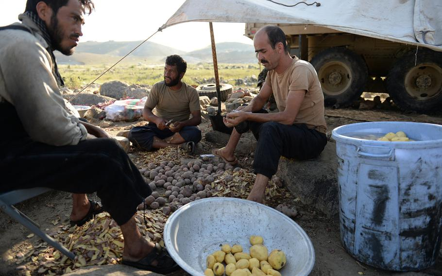 Afghan National Army soldiers peel potatoes at a forward field camp during an operation in Nangarhar province in August 2015. Some men join the army as a way to make money but find the danger and hard lifestyle difficult.