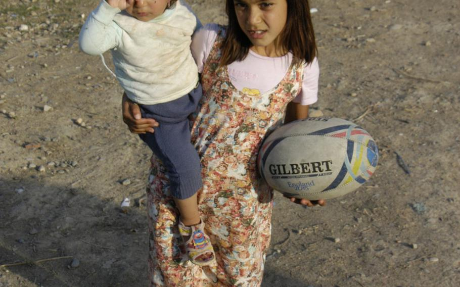 This young Yazidi girl has her hands full, with a rugby ball in one hand, and a toddler in the other at a camp for displaced people in Irbil, Iraq, on Oct. 25, 2015.