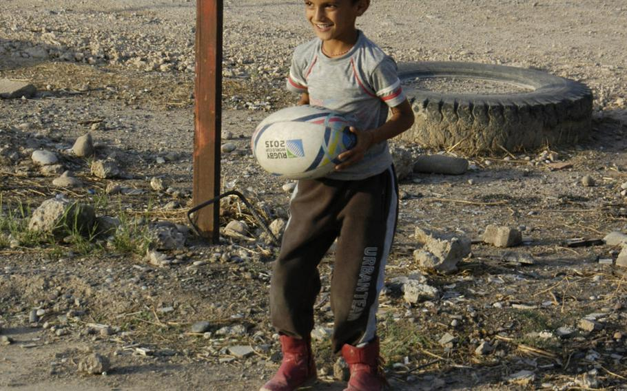 A Yazidi boy smiles as he prepares to show off his rugby skills at a camp for displaced people in Irbil, Iraq, Oct. 25, 2015.