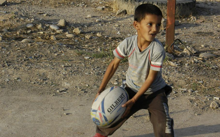 A Yazidi boy prepares to throw a rugby ball at a camp for displaced people in Irbil, Iraq, Oct. 25, 2015.