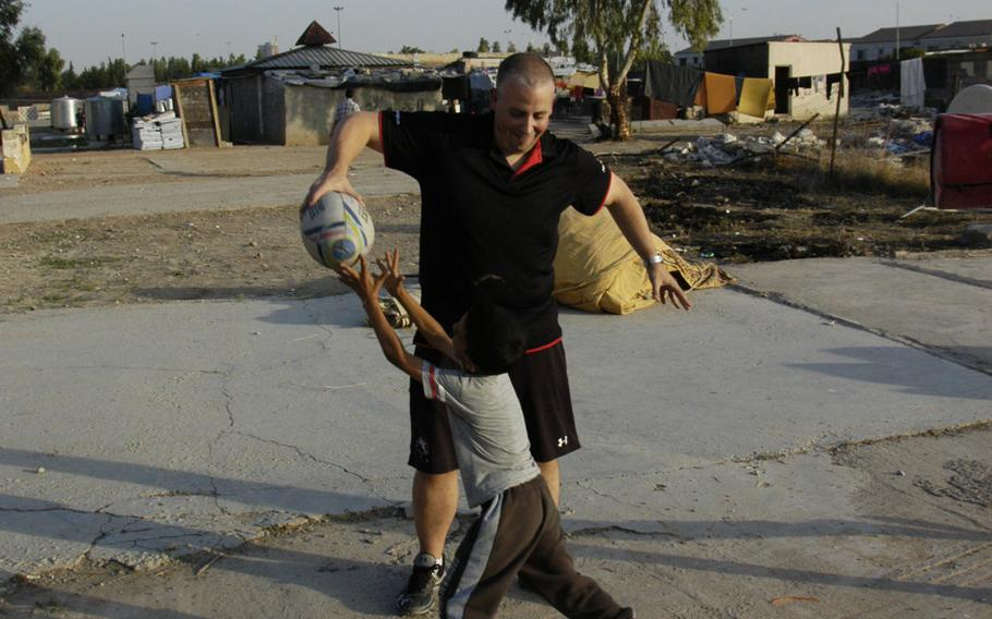 Logistics company worker Neil Young, of Scotland, plays rugby with a Yazidi boy at a camp for displaced people in Irbil, Iraq, on Sunday, Oct. 25, 2015.
