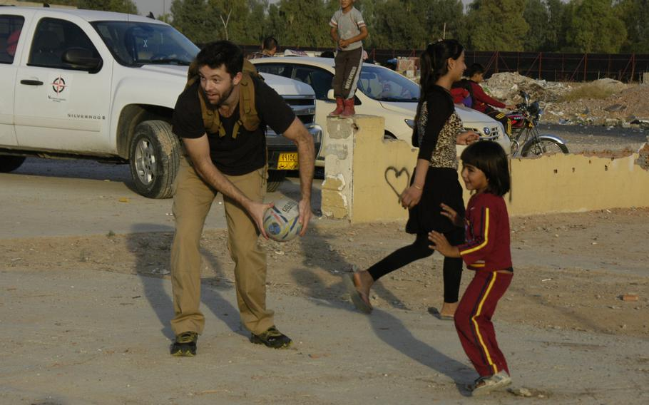New Zealander Campbell MacDiarmid plays rugby with Yazidi children at a camp for displaced people in Irbil, Iraq, on Sunday, Oct. 25, 2015.