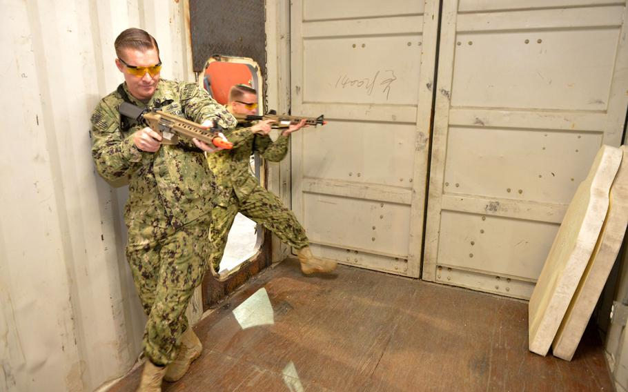 Coast Guardsmen Petty Officer 2nd Class Philip Cook, left, and Petty Officer 3rd Class Jake Brasker, from Patrol Forces Southwest Asia's Maritime Engagement Team, demonstrate boarding procedures in a facility is known as the ship-in-a-box on March 12, 2019 in Bahrain.