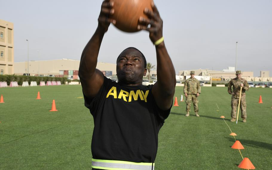 Army Spc. Armel Joakim whips a rubber ball backwards as part of the new Army fitness test, conducted as a test run during deployment to Camp Arifjan, Kuwait, March 23, 2019.