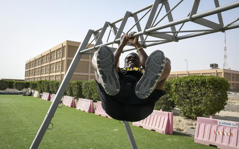 Army Spc. Armel Joakim crunches his legs upward as part of the new Army fitness test, conducted as a test run during deployment to Camp Arifjan, Kuwait, March 23, 2019. The new test allows him to show off his strength, and allows him more time to pass his run, he said.