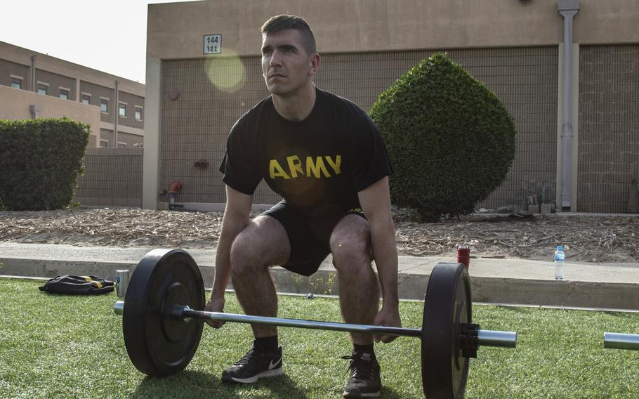 Army Staff Sgt. Raymond Edel begins the deadlift portion of the new Army fitness test, conducted as a test run during deployment to Camp Arifjan, Kuwait, March 23, 2019.