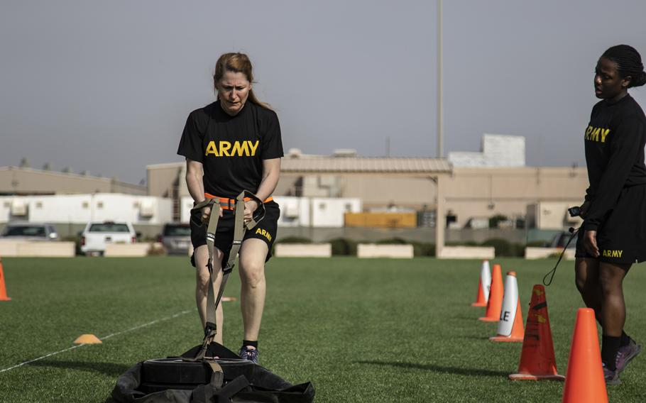 Lt. Col. Kristen Auge drags a 90-pound weight across turf as part of the new Army fitness test, conducted as a test run during deployment to Camp Arifjan, Kuwait, March 23, 2019. The new fitness test will require more training and more effort to pass, said Auge, 51, commander of the headquarters battalion of the 34th Infantry Division of the Minnesota National Guard.