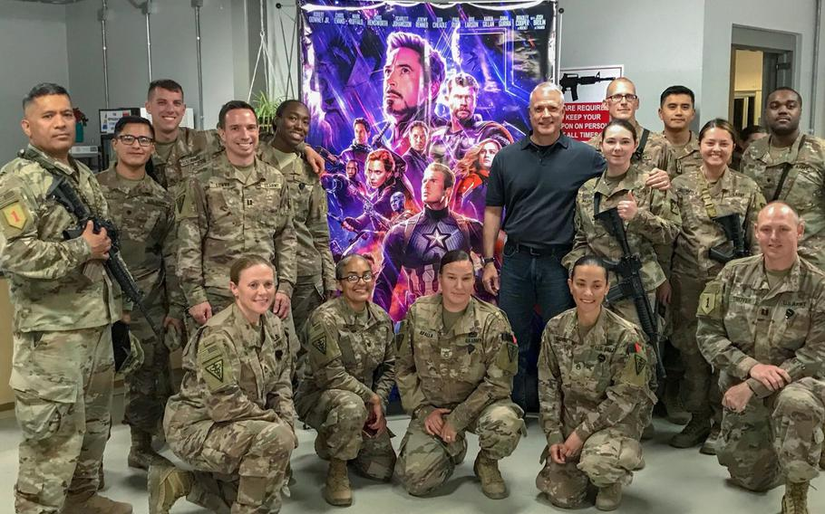 """Troops deployed to Bagram Air Field prepare to watch the movie """"Avengers: Endgame,"""" which was brought to Afghanistan by Ken Caldwell, center, senior vice president of North American theatrical distribution for the Army and Air Force Exchange Service."""