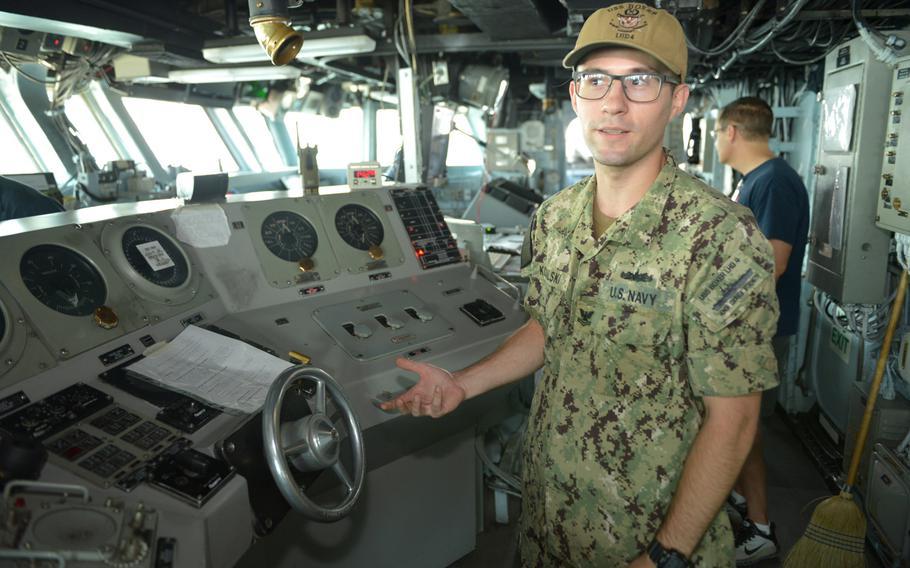 Petty Officer 2nd Class Jeremy Kowalski explains bridge operations on board the amphibious assault ship USS boxer on Aug. 1, 2019.