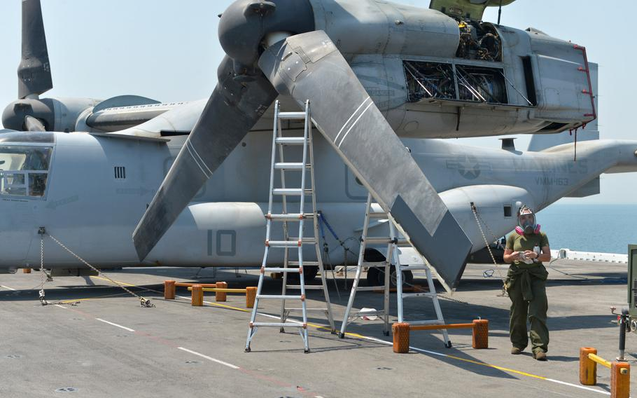 A Marine conducts maintenance on a MV-22 Osprey tilt-rotor aircraft on board the amphibious assault ship USS Boxer on Aug. 1, 2019. The Boxer pulled into Bahrain on July 25 for a scheduled weeklong port visit just days after crew members downed at least one drone during inbound transit through the Strait of Hormuz.