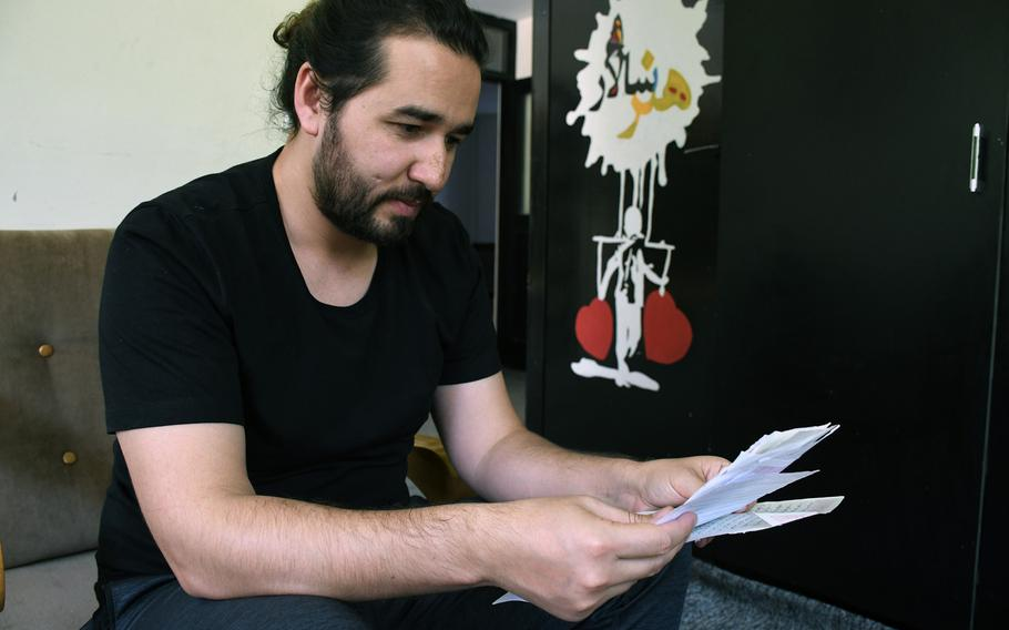 Omaid Sharifi on Thursday, Aug. 1, 2019, reads letters collected as part of a campaign that aims to share Afghans' worries and recommendations with negotiators at peace talks.