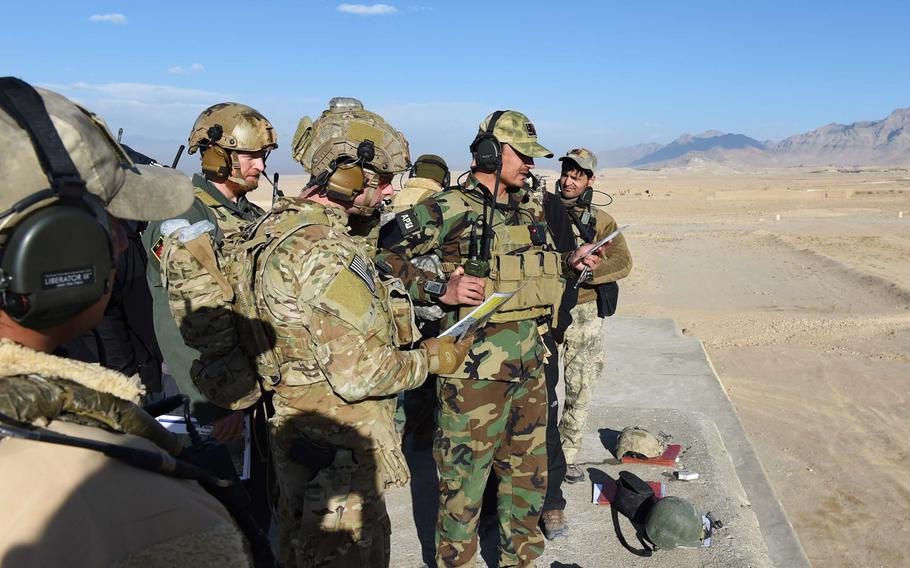 Under the supervision of two U.S. Army trainers, a student in a training program for Afghan Tactical Air Coordinators practices calling in an airstrike in 2016. According to a new Defense Department report, U.S. and coalition forces have failed to adequately develop the Afghans' airdrop capabilities.