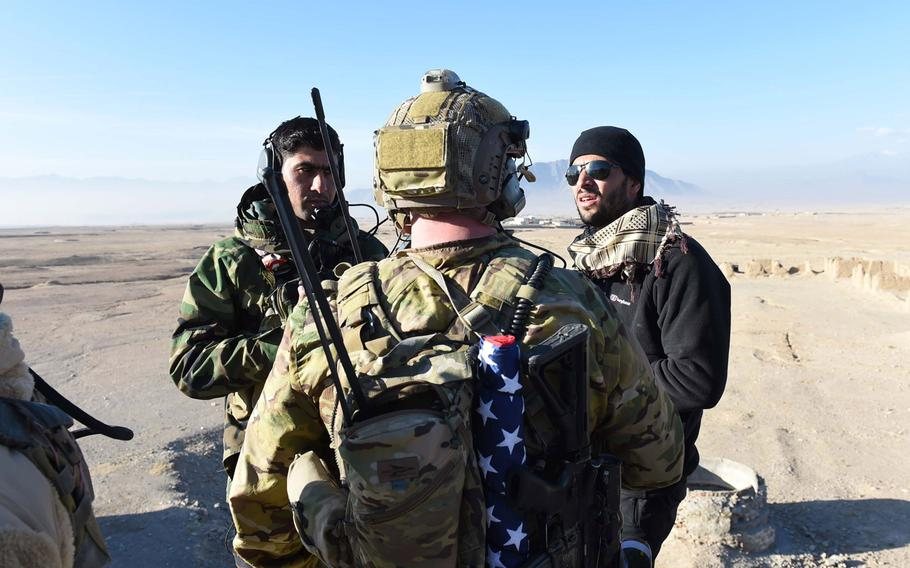 A U.S. Army trainer consults with an interpreter and a student in a training program for Afghan Tactical Air Coordinators during an exercise in 2016. According to a new Defense Department report, U.S. and coalition forces have failed to adequately develop the Afghans' airdrop capabilities.