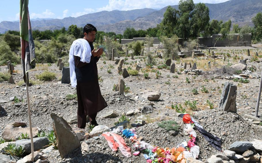 Afghan soldier Nematullah prays at a grave in his family's cemetery in Kunar province on Aug. 17, 2019. The family say they buried someone in the grave last year who they thought was him.
