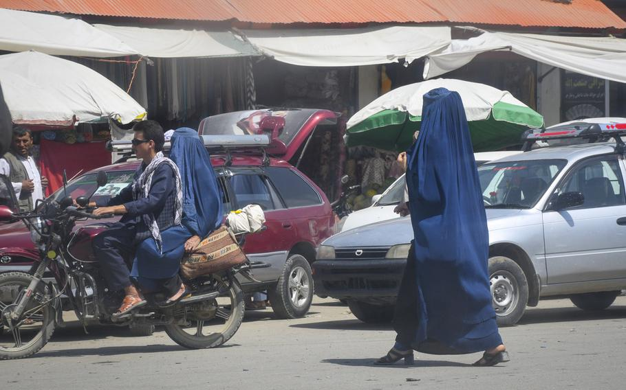 """A local woman wears high heels under a chadaree, or Afghan burqa, as she walks through the markets of Faizabad, the provincial capital of remote Badakhshan province, July 15, 2019. Despite a Taliban statement early this year that said the group is """"committed to all rights of women,"""" locals in Badakhshan have said that, in the parts of the province controlled by the group, girls aren't allowed to go to school after sixth grade."""