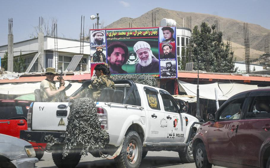 Afghan police pass by depictions of noted anti-Taliban leaders Ahmad Shah Masoud and Burhanuddin Rabbani, July 15, 2019, as they drive through the streets of Faizabad, the provincial capital of remote Badakhshan province.